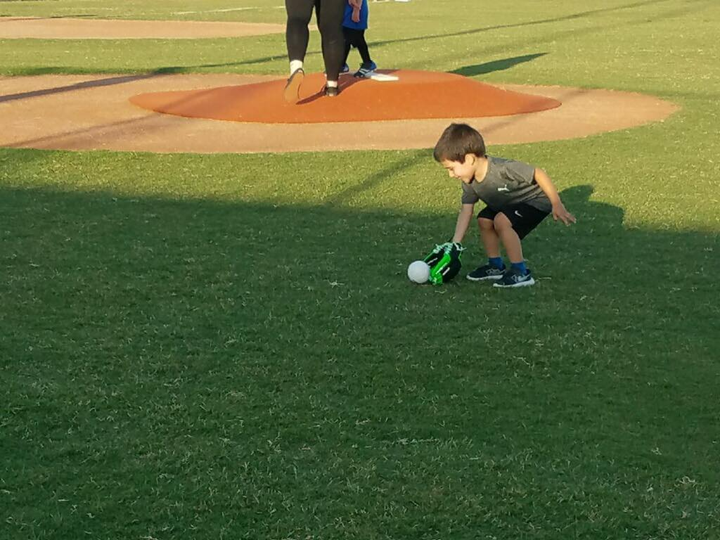 Young boy picking up baseball