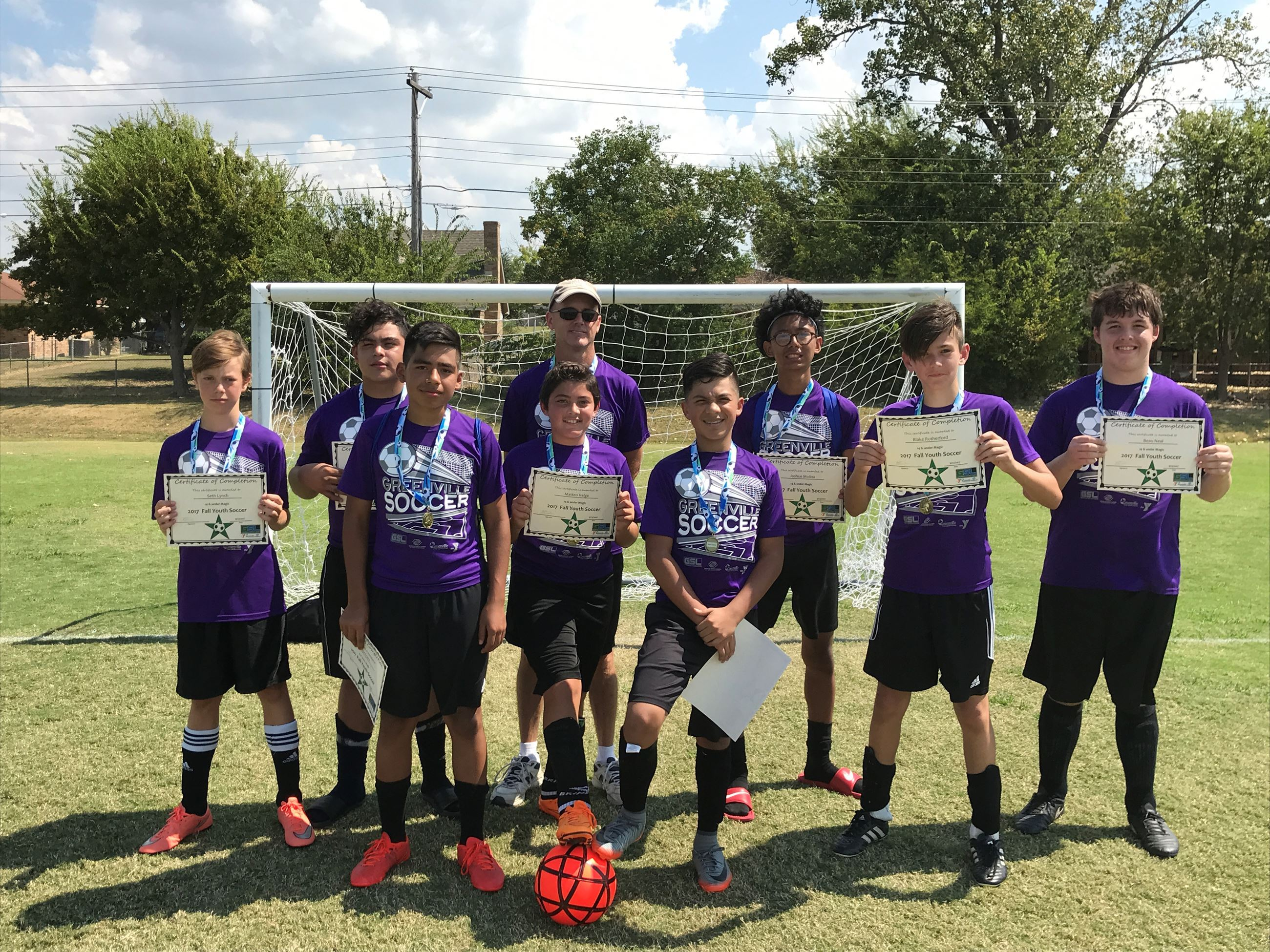Boys soccer team in purple with certificates
