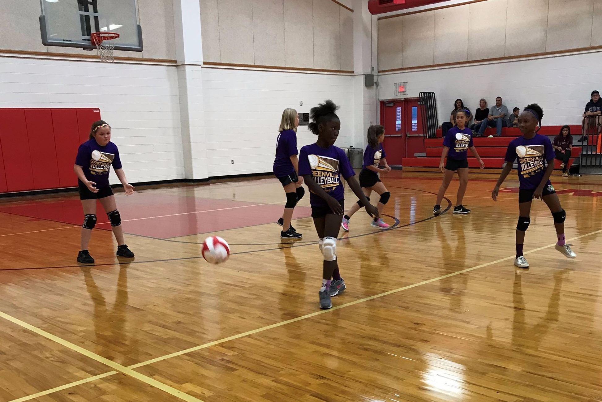 Girls playing volleyball wearing purple